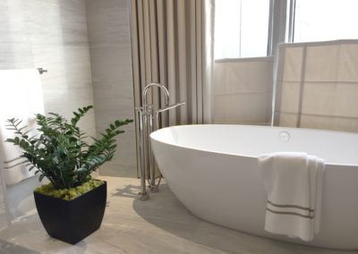 A modern bathroom with a ZZ plant in a matte black container, next to a white oval bathtub in front of big windows.
