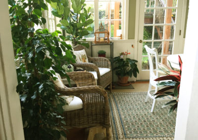 An image of a lush residential sunroom plantscaped with several potted indoor plants around furniture with windows all around.