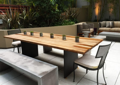 An outdoor modern patio with a large wooden table with six small potted succulent plants in tin containers.